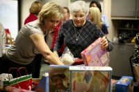 The wives of two UF surgeons, Patti Behrns, left, and Susan Rout, right, delivered gifts to Shands at UF Child Life program on Dec. 17.