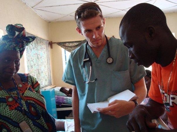 UF medical student, John Martino (center) and translator, Sana (right), talks to a mother (not pictured) who's child is suspected of having malaria.