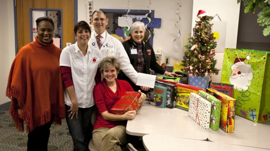 (left to right) Kevin Behrns,M.D., chairman of the department of surgery; development director Kimberly Hankerson, director of development; and wives of UF surgeons, Janice Nelson, Patti Behrns and Susan Rout pose proudly with a small portion of gifts collected for the young patients. Photo by Sarah Kiewel