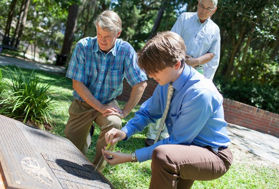 The 2014 Hippocratic Award winner, Robert Hatch, M.D., watches as fourth-year medical student Philip Gilbo adds a new nameplate to the boulder in Wilmot Gardens, which holds the names of previous award winners. Photo by Jesse S. Jones