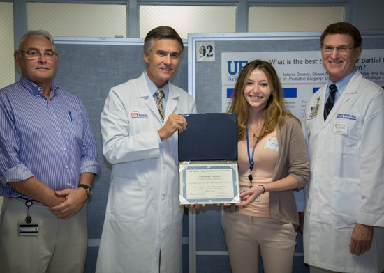 Amanda Sacino, an M.D., Ph.D., third-year medical student, receives her first-place award, which was presented by, from left, Joseph Fantone, M.D., UF College of Medicine Dean Michael Good, M.D., and Greg Schultz, Ph.D. Photo by Charles Poulton.