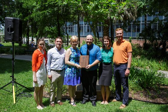 Members of the class of 2016 present the Christensen family with the Hippocratic Award at UF's Wilmot Gardens. Photo by Mindy C. Miller